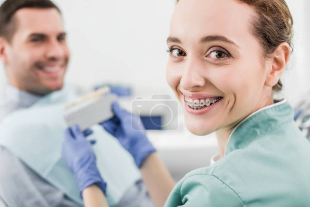 selective focus of cheerful dentist with braces on teeth smiling while holding color palette near patient