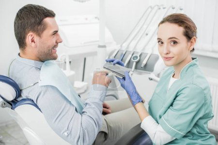 happy patient pointing with finger at teeth color palette near dentist