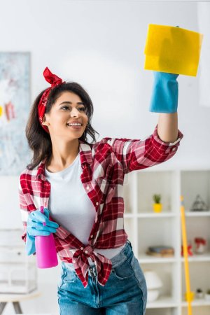 Photo for Smiling african american woman in plaid shirt and blue rubber gloves cleaning house with yellow rag - Royalty Free Image