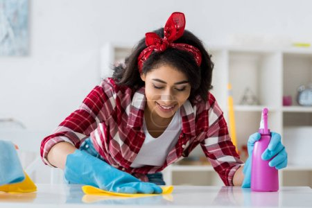 Photo for Pretty african american woman cleaning table with yellow rag - Royalty Free Image