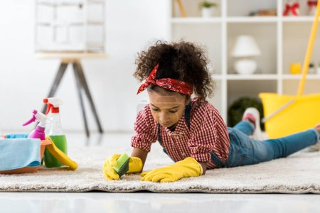 selective focus of cute african american girl lying on carpet and cleaning it with sponge