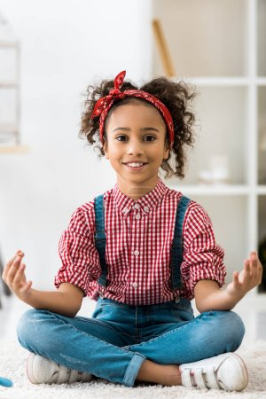Photo for Smiling african american child sitting in lotus pose and looking at camera - Royalty Free Image