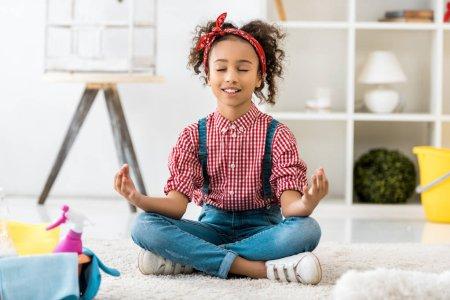 Photo pour Adorable enfant afro-américain assis en posture de lotus avec les yeux fermés - image libre de droit