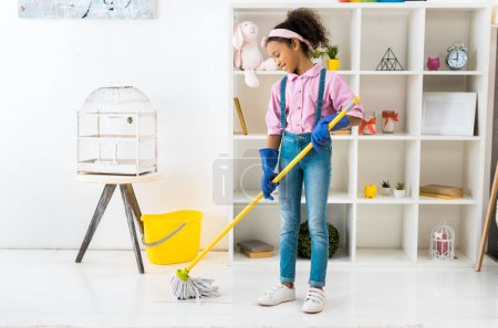 Photo for Smiling african american child washing floor with mop - Royalty Free Image