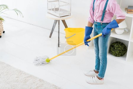 Photo for Partial view of african american girl in blue rubber gloves washing floor with broom - Royalty Free Image