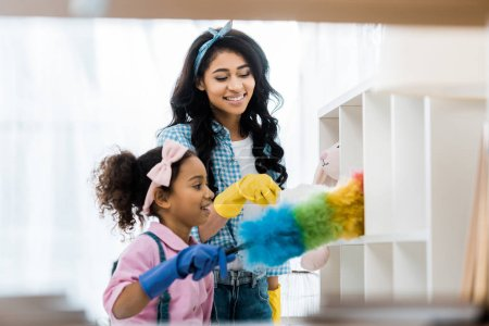 Photo for Pretty african american woman with daughter cleaning house - Royalty Free Image