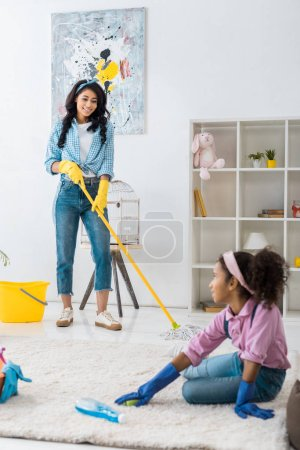 Photo for Cute african american child cleaning carpet while mother washing floor - Royalty Free Image