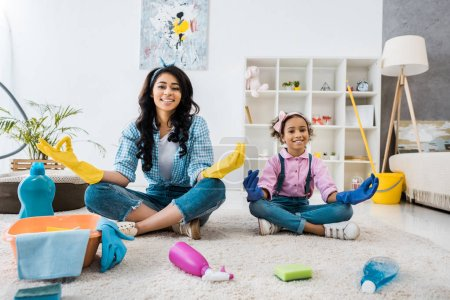 Photo for Smiling african american mother and daughter in bright rubber gloves sitting on carpet in lotus poses - Royalty Free Image
