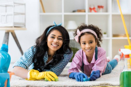 Photo for Smiling african american woman and daughter in bright rubber gloves lying on carpet - Royalty Free Image
