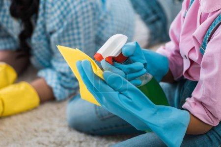 vista recortada de niños afroamericanos rociando líquido de limpieza sobre trapo de goma amarillo