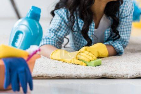 vista recortada de mujer afroamericana en guantes de goma amarillos acostados en la alfombra con esponja