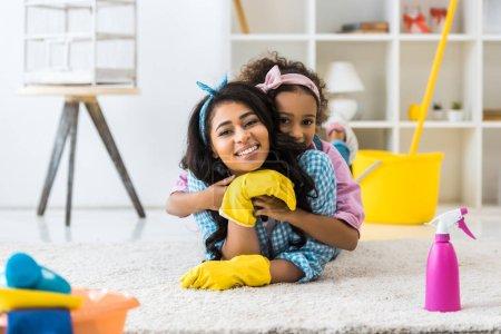 entzückendes afrikanisch-amerikanisches Kind umarmt Mutter auf Teppich liegend
