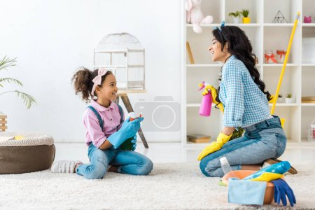 Photo for African american mom and child holding spray bottles while sitting on carpet - Royalty Free Image