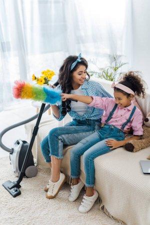 Photo pour Mignon enfant afro-américain assis sur le canapé avec une mère souriante et tenant des plumeaux colorés - image libre de droit