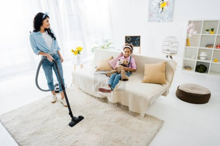 Photo for African american mother cleaning carpet with vacuum cleaner while daughter sitting on sofa - Royalty Free Image