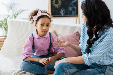 Photo pour Grave mère afro-américaine et l'enfant parler lors de l'assise sur le canapé à la maison - image libre de droit