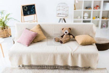Photo pour Salon confortable avec oreillers et ours en peluche assemblés sur un canapé confortable - image libre de droit