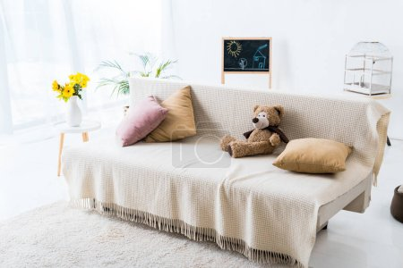 Photo for Light spacious room with comfortable sofa with pillows and teddy bear - Royalty Free Image