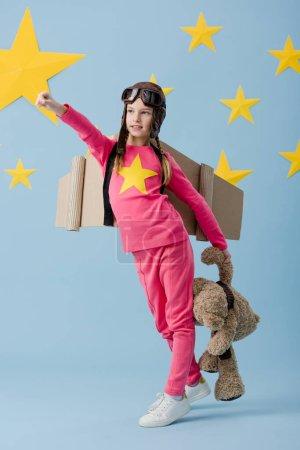 Kid in flight helmet funny posing with teddy bear on blue starry background