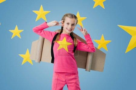 Photo pour Rire d'enfant avec des ailes en carton montrant le signe de la paix sur fond étoilé bleu - image libre de droit