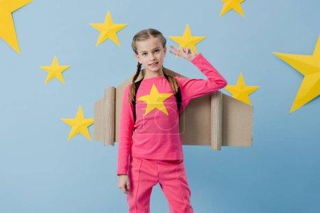 Photo pour Un enfant heureux avec un carton ailes montrer signe de paix sur fond étoilé bleu - image libre de droit