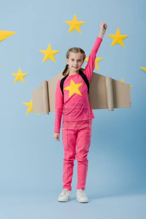 Photo for Joyful kid with cardboard wings standing with fist up on blue background with stars - Royalty Free Image