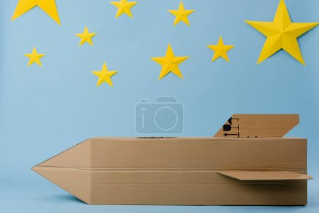 Cardboard rocket and yellow stars on blue starry background