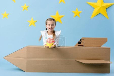 Photo for Smiling kid with cardboard rocket holding yellow star on blue starry background - Royalty Free Image