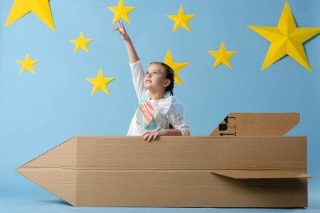 Niño con cohete de cartón apuntando con el dedo a la estrella sobre fondo azul estrellado