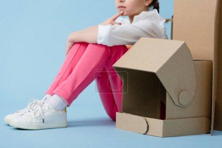 Photo pour Vue recadrée d'un enfant coûteux assis avec un casque en carton sur fond bleu - image libre de droit