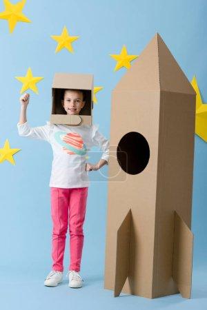 Photo pour Enfant inspiré dans un geste de casque près de fusée en carton sur fond bleu étoilé - image libre de droit