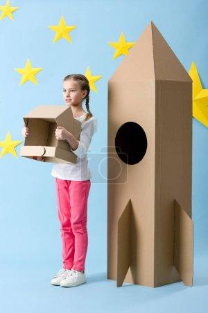 Photo pour Enfant inspiré debout près d'une grosse fusée en carton et tenant un casque sur fond bleu étoilé - image libre de droit