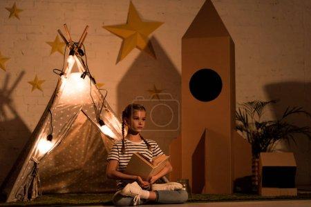 Photo pour Enfant détendu assis dans une pose de lotus et lisant un livre dans une pièce sombre - image libre de droit