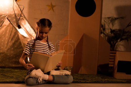 Photo for Preteen child sitting in lotus pose and reading book in dark room - Royalty Free Image