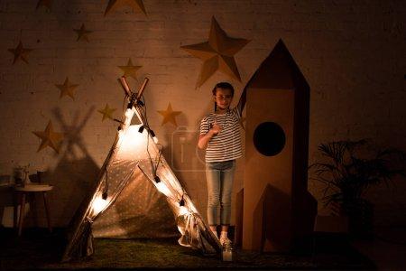 Photo pour Enfant debout entre wigwam et fusée en carton dans la pièce sombre - image libre de droit