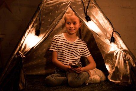 Photo pour Enfant heureux avec smartphone assis dans wigwam confortable à la maison - image libre de droit