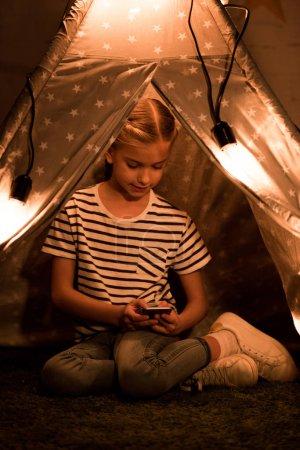 Photo pour Enfant en t-shirt rayé à l'aide d'un smartphone assis en wigwam dans une pièce sombre - image libre de droit