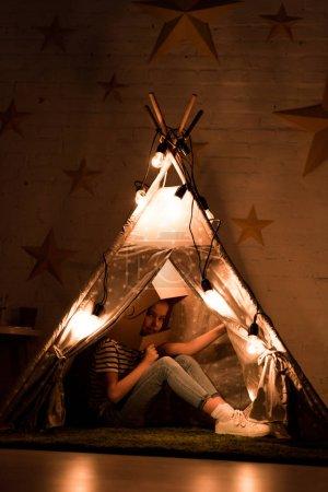 Photo pour Preteen enfant en carton casque assis dans wigwam dans la chambre noire - image libre de droit