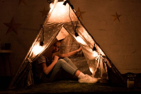 Photo pour Preteen enfant assis dans wigwam confortable avec des ampoules dans la chambre noire - image libre de droit