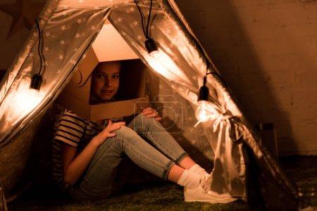 Photo pour Mignon enfant en carton casque assis dans wigwam avec des ampoules dans la chambre noire - image libre de droit