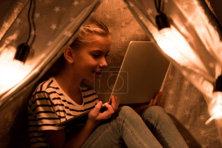 Photo for Cheerful kid using laptop in wigwam at home - Royalty Free Image