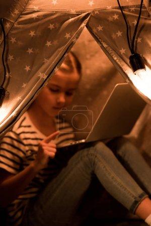 Photo pour Preteen enfant en utilisant un ordinateur portable tout en étant assis dans wigwam à la maison - image libre de droit