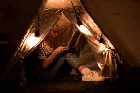 Photo pour Enfant utilisant un ordinateur portable tout en étant assis dans wigwam dans la pièce sombre - image libre de droit