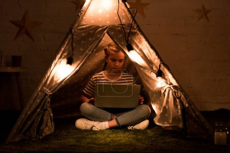 Photo pour Enfant concentré utilisant un ordinateur portable en wigwam avec des ampoules lumineuses - image libre de droit
