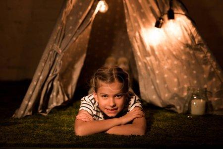 Photo pour Enfant riant couché sur le tapis dans la chambre noire et regardant la caméra - image libre de droit