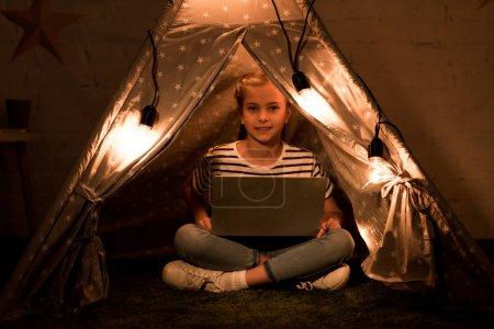 Photo pour Enfant heureux utilisant un ordinateur portable tout en étant assis dans wigwam dans la chambre noire - image libre de droit
