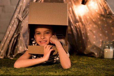 Photo pour Enfant insouciant dans un casque en carton couché sur le tapis et regardant la caméra - image libre de droit