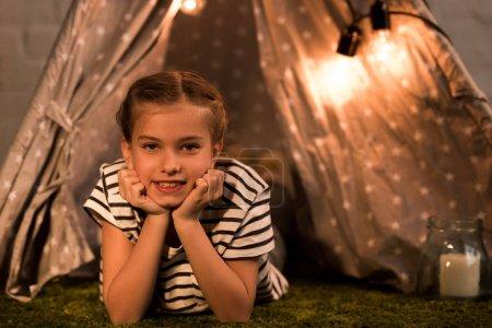 Photo pour Enfant rêveur couché sur le tapis et regardant la caméra à la maison - image libre de droit