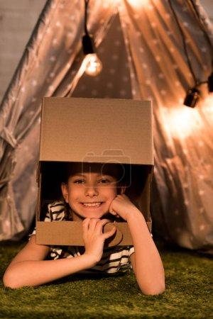Photo pour Enfant riant dans un casque en carton couché sur un tapis vert - image libre de droit