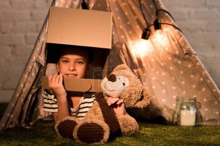 Photo pour Enfant curieux dans le casque en carton couché sur le tapis avec ours en peluche - image libre de droit